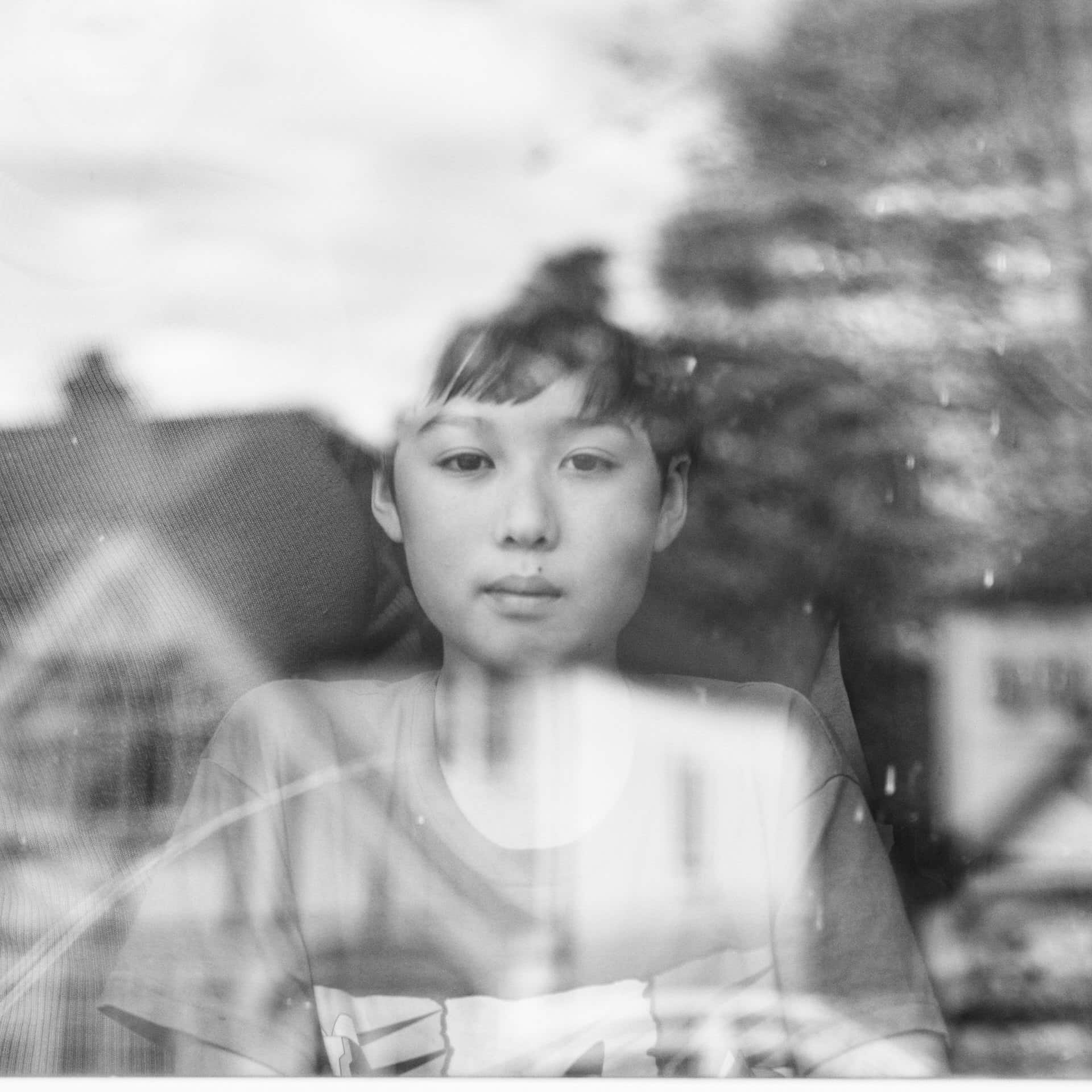 Asian boy behind window with reflections from outside during Corona Virus