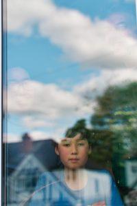 boy looking outside through window during Corona virus