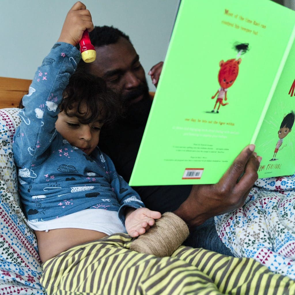 Father reading to son in bed from a children's book with a BAME protagonist.