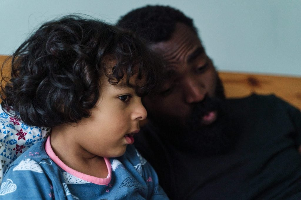 Close-up of father reading to son in bed from a children's book with a BAME protagonist.