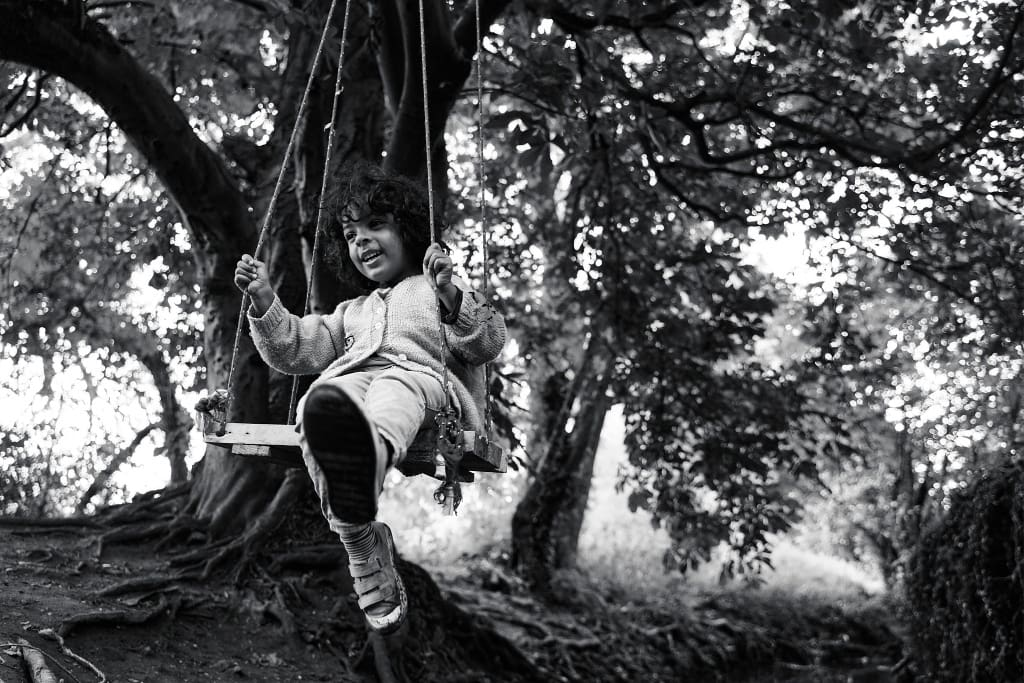 Photograph of a child swinging on a swing hanging in a forest.