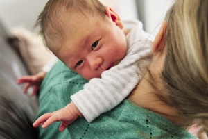 Baby being burped on the shoulder of mother during a newborn documentary family photoshoot.