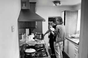 Father kissing baby while cooking during a Family and baby photography photoshoot in Bromley
