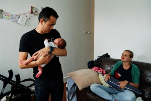 Father holding newborn to give to mother for a feed during a newborn photography shoot.