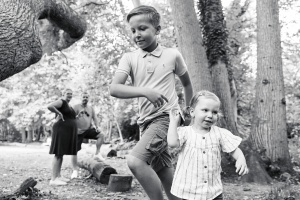 Children playing with parents looking at them from the background during a family photography session at Scadbury Park in Chislehurst