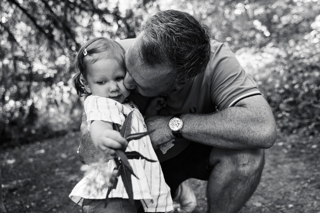 Father kisses daughter during a family photography session in Chislehurst