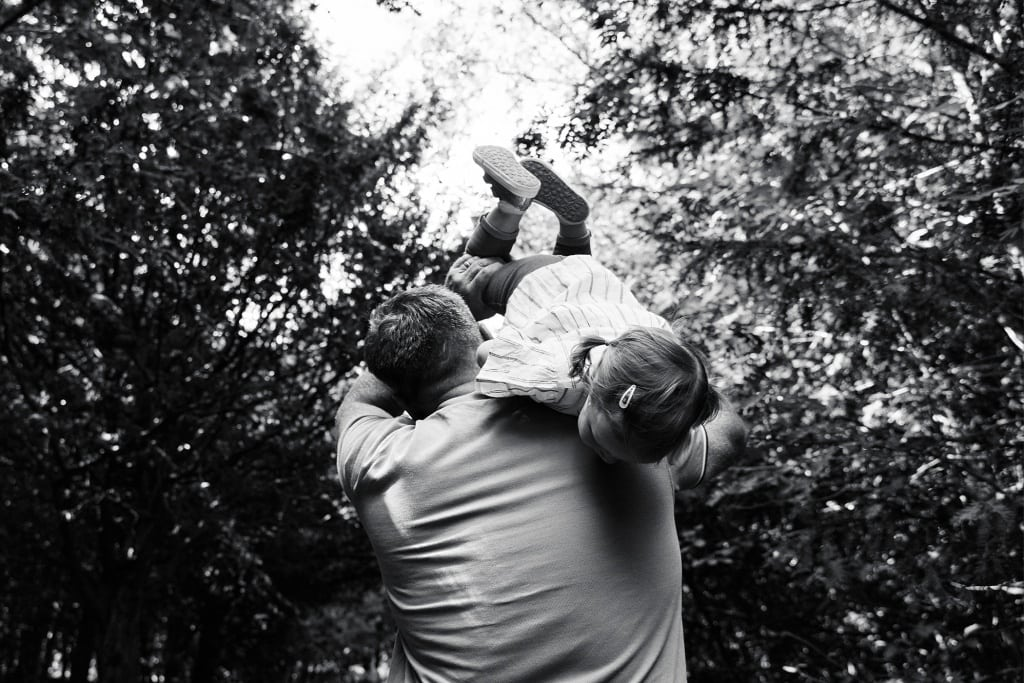Father carries child over his shoulder during a candid family photography session in Chislehurst Bromley