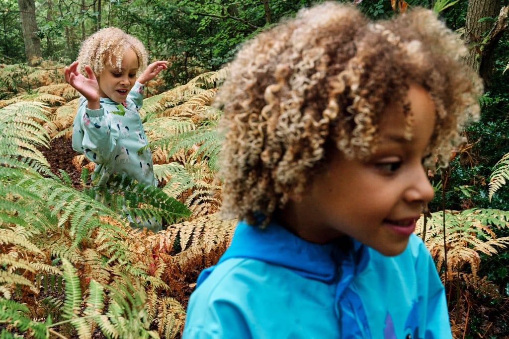 Girls walking through ferns at Hayes Common during a family photography session at Hayes Common in Bromley