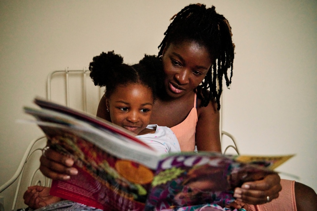 Mother and daughter reading a book during a natural family photography session in Rochester Kent