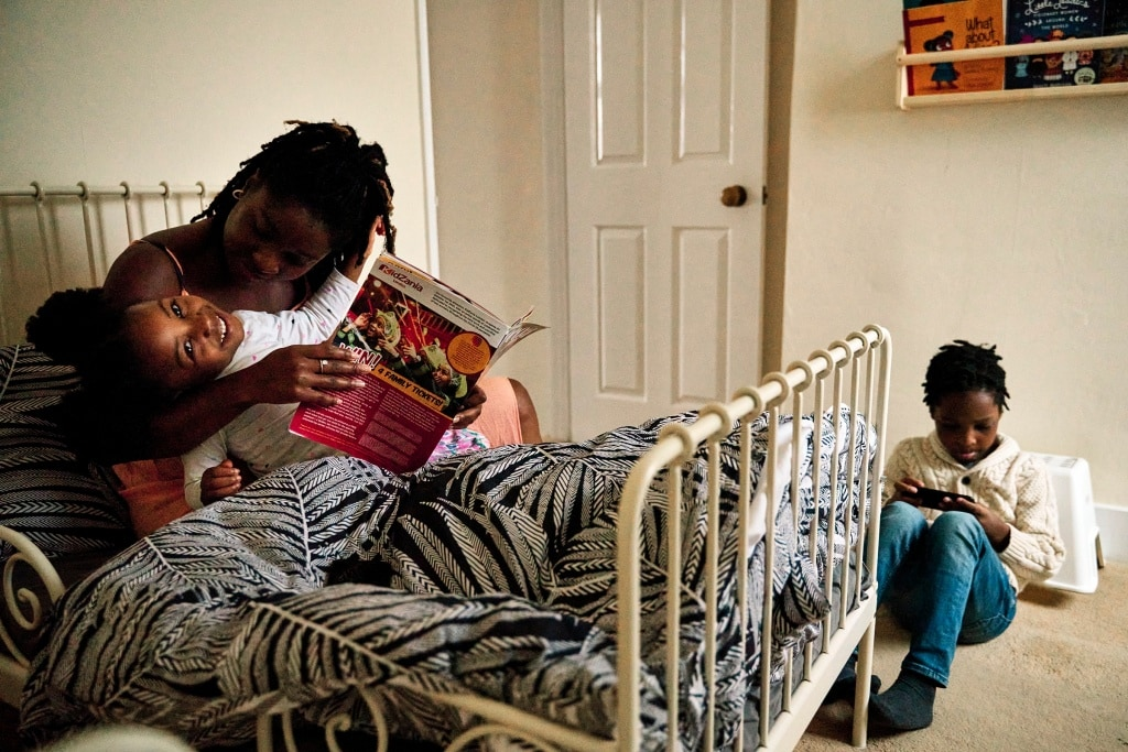 Mother and child reading together on the bed during a family photoshoot in Rochester Kent