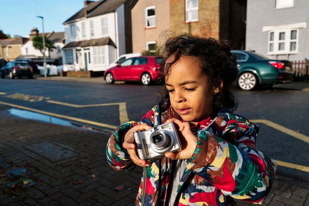 Child with a camera taking photographs during a Christmas scavenger hunt in Bromley London.