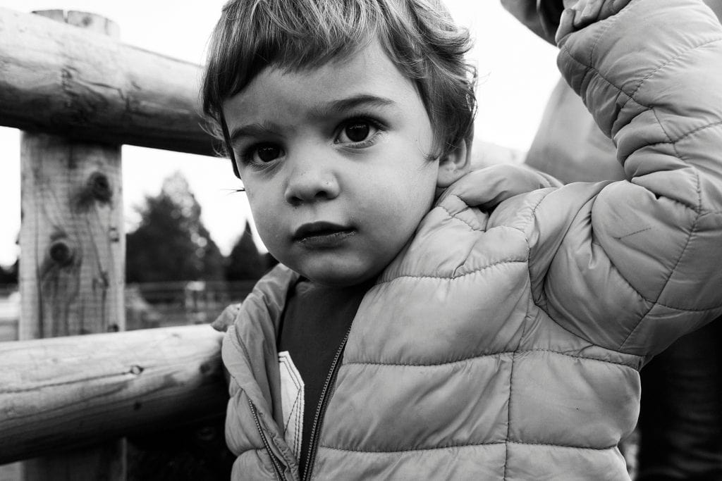 A portrait of a small child looking into the camera during a family photography session in Bromley.