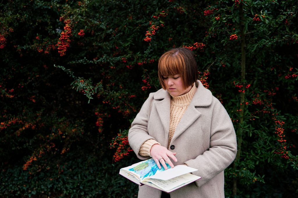 An artist looking through her journal during a personal branding photography session in Dulwich Park in London.