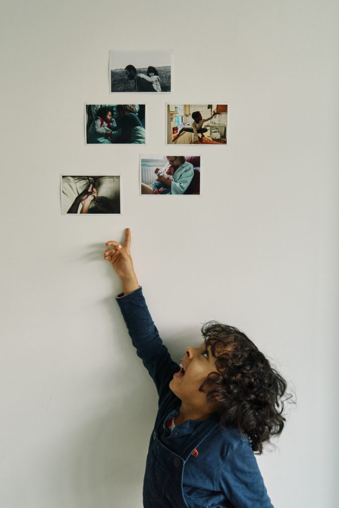 My son pointing to my 5 favourite photographs of 2020 hanging on the wall.