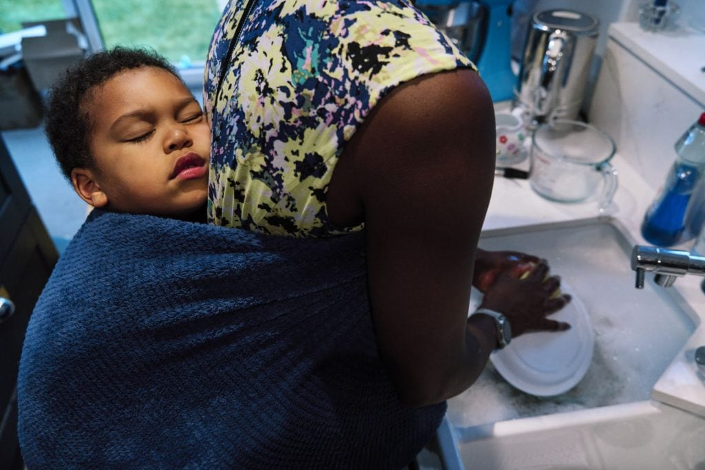 Family photograph of a mother doing the dishes while child is sleeping on her back.
